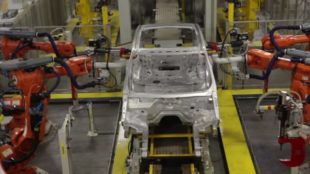 various shots robotic arms work on the aluminium body shell of a range rover sport automobile as it moves along the assembly line at the jaguar land... - plc stock videos & royalty-free footage
