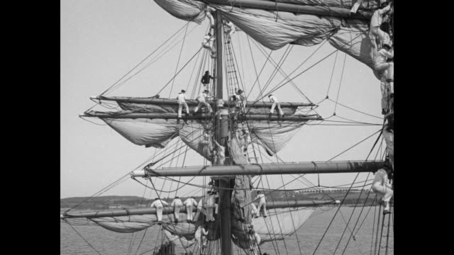 various shots sailors climbing on schooner's rigging unfurling sails / sailors on deck pulling lines hauling up sails / sailors on mast as sail rises... - schiffsmast stock-videos und b-roll-filmmaterial