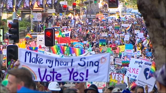 various shots same sex marriage rally sydney huge crowds march along behind banner make my heart sing vote yes colourful crowds banner and signs... - 法点の映像素材/bロール