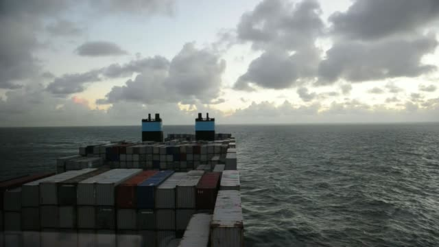 vídeos de stock, filmes e b-roll de various shots shipping containers stand aboard the maersk mckinney moeller triplee class container ship operated by ap moellermaersk a/s as it sails... - de perna aberta