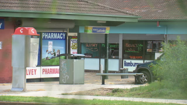 various shots small suburban shopping area vs Shalvey shops incl Pharmacy NSW Lotteries sign public phone booth