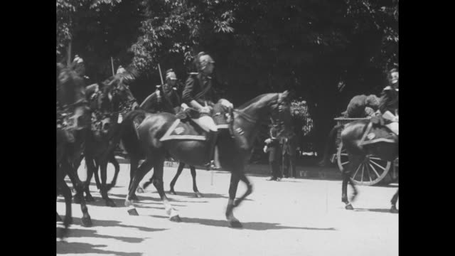 various shots soldiers on horseback parading down street buildings in bg / lines of mounted soldiers from behind filling street car parked at curb... - ceremonial robe stock videos and b-roll footage