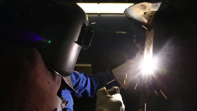 various shots sparks fly as an apprentice wearing a protective vizor welds a metal joint at alstom sas welding training facility in stafford, uk, on... - trainee stock videos & royalty-free footage