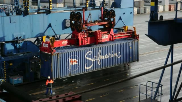 vídeos de stock, filmes e b-roll de various shots straddle carriers operate on the dockside beside the maersk mckinney moeller triplee class container ship operated by ap moellermaersk... - de perna aberta