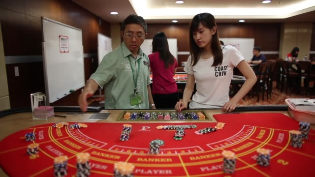 Various shots students handle gaming chips while learning the game of blackjack at the Macao Polytechnic Institute MPI Gaming Teaching and Research...