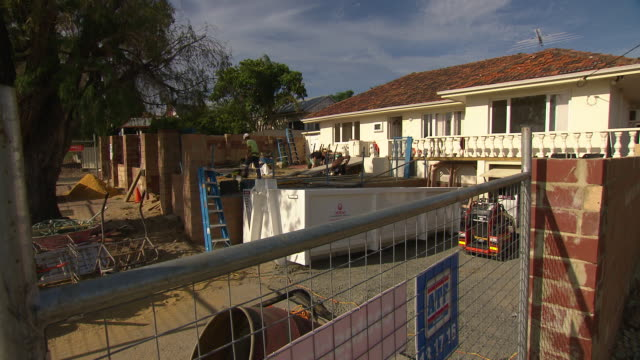 various shots suburban house renovation building site seen through security fence includes cement mixer bobcat in driveway ladders wheelbarrow pile... - cement mixer stock videos and b-roll footage