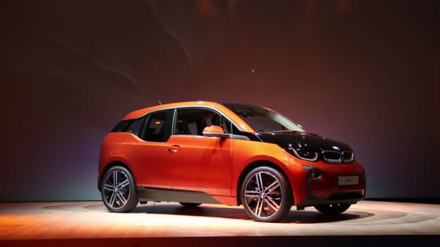 Various shots the BMW i3 the electric automobile produced by Bayerische Motoren Werke AG sits on the stage covered by a blue cloth prior to being...