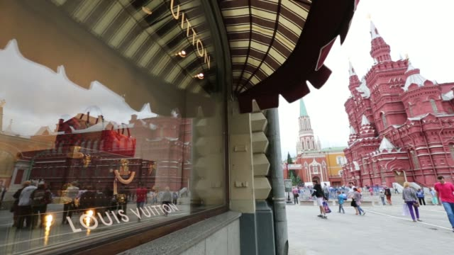 various shots the kremlin and pedestrians walking by are reflected in the window of a louis vuitton store, operated by lvmh moet hennessy louis... - ブランド ルイヴィトン点の映像素材/bロール