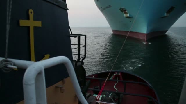 various shots the tugboat hermes uses a mooring line to guide the prow of the maersk mc kinney moller triple e class container ship operated by ap... - monday morning stock videos & royalty-free footage