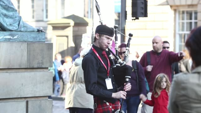 stockvideo's en b-roll-footage met various shots tourists watch and walk past a man playing bagpipes and wearing a kilt in edinburgh, uk, on saturday, aug 9, 2014 - alle vlaggen van europa