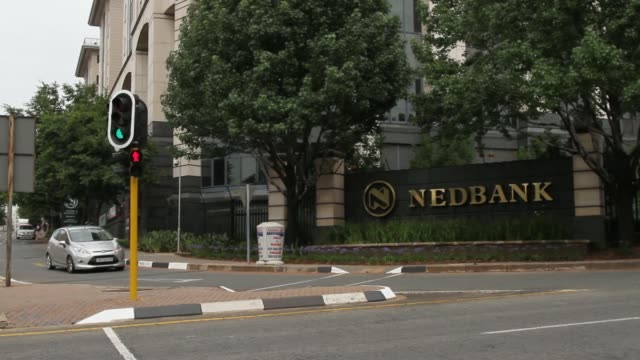 various shots traffic passes the headquarters of nedbank group ltd. banking group stands in the sandton district of johannesburg, south africa, on... - banking sign stock videos & royalty-free footage