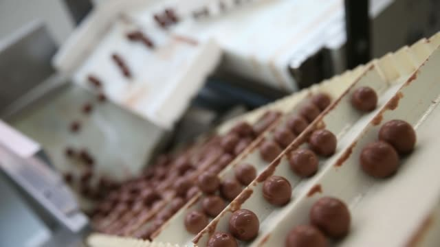 Various shots unwrapped Lindor chocolate balls move along the production line inside the Lindt Spruengli AG factory in Kilchberg Switzerland on...