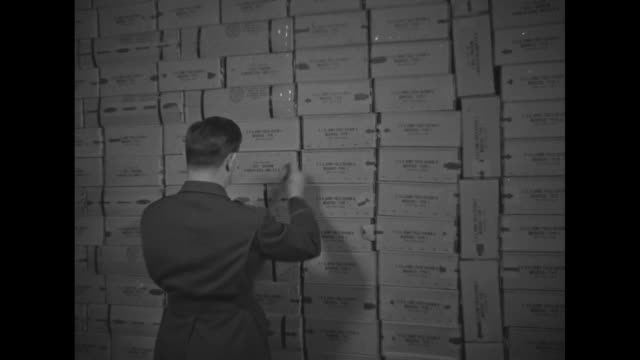 various shots us army officer checking inventory of stacks of boxes of army field rations / cu officer checking off boxes / various shots boxes... - army video stock e b–roll