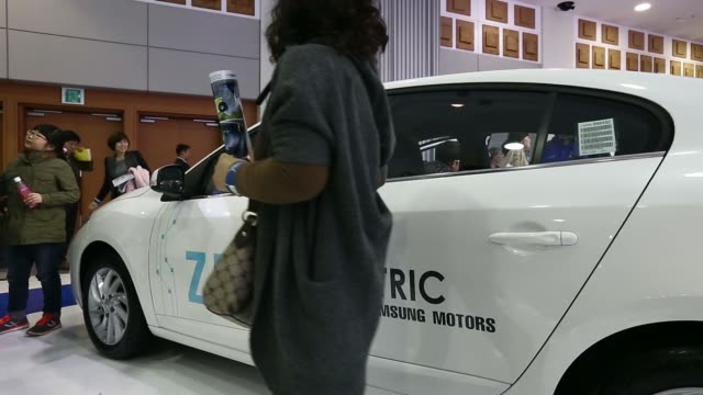 vídeos de stock, filmes e b-roll de various shots visitors look at a renault samsung motors co. sm3 z.e. electric vehicle on display at the first international electric vehicle expo in... - generation z