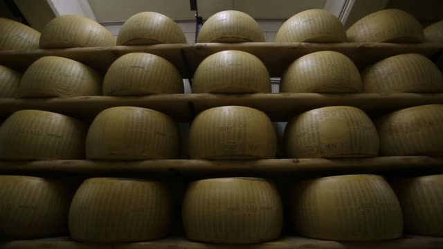various shots whole parmigiano reggiano cheeses sit on storage racks during the aging process at coduro cheesemakers in fidenza, italy, on thursday,... - parmesan stock videos & royalty-free footage