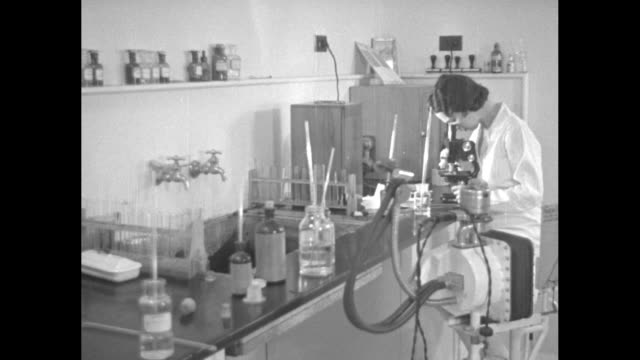 vídeos de stock, filmes e b-roll de various shots woman in lab coat looks into microscope, man in lab coat works with pipettes and test tube, bottles, flasks, funnels and other lab... - 1920