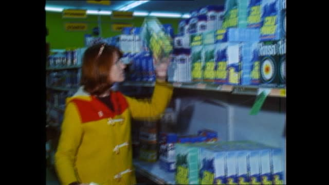 various shots woman with trolley in supermarket at washing powder section see on shelf Rinso Cold Power woman shopper inspects pack / close up Omo...