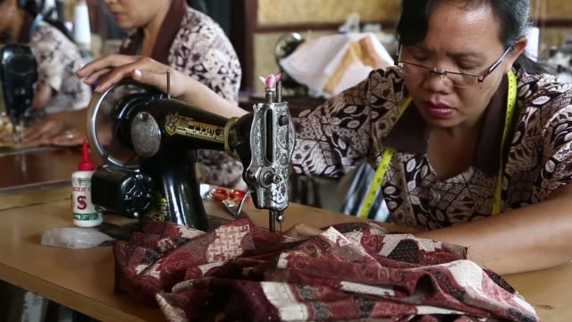 various shots workers make batik clothing with sewing machines at a store in gianyar bali indonesia on tuesday oct 8 workers paint batik cloth a male... - batik stock videos and b-roll footage