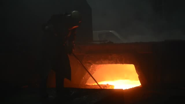 Various shots workers operate in the blast furnace in Voestalpine AG's steel plant in Linz Austria on Wednesday July 24 Red hot flames and smoke in...