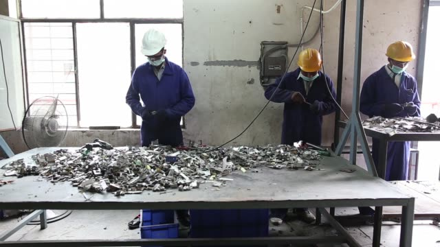 various shots workers use pliers and drills to separate component parts of electronic waste at the attero recycling pvt facility in the raipur... - e waste stock videos & royalty-free footage
