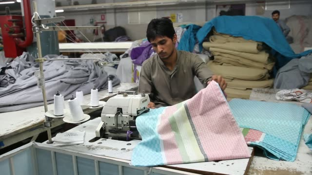 Various shots workers use sewing machines to make quilt covers and mattress covers at the Faisal Fabrics Ltd factory in Khurrianwala Punjab Pakistan...