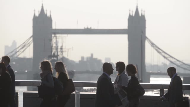 vídeos de stock, filmes e b-roll de various side views commuters walking over london bridge on their way to work during the morning rush hour as tower bridge stands in the background in... - produto interno bruto