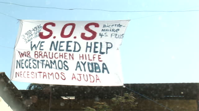 various sos signs for help in haiti after the earthquake / sign saying 'sos help 20 morts' / graffiti on building 'we need help' / banner hanging... - haiti stock-videos und b-roll-filmmaterial