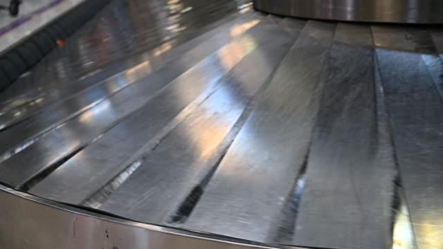 vidéos et rushes de plusieurs valises sur le tapis roulant à l'aéroport international - convoyeur