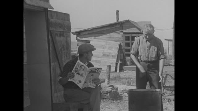 a seated man in a newsboy's cap reading from vogue magazine as another washes clothing at a squatter's camp the man reads that someone paid $15000... - great depression stock videos & royalty-free footage