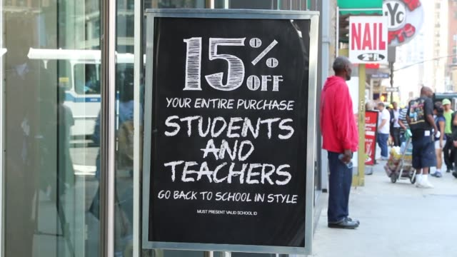 Various tight shots of a sidewalk sign advertising a back to school sale with various retail stores in the background including HM as pedestrians...