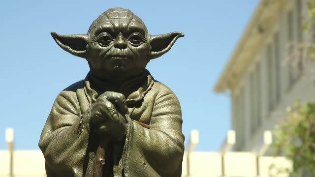 Various tight shots of a Yoda statue atop a fountain at the Lucasfilm Ltd campus in San Francisco California on a clear sunny day