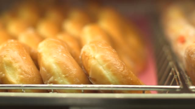 various tight shots of various dunkin donut products in canton, ma on september 20 a tight slow motion tracking shot of jelly and glazed doughnuts in... - blueberry muffin stock videos & royalty-free footage