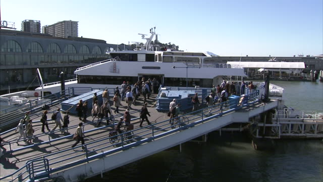 various unidentifiable people on dock pier walking boarding ferry boat in dock at the san fran ferry building port ca harbor san francisco bay area - san francisco ferry building stock videos & royalty-free footage