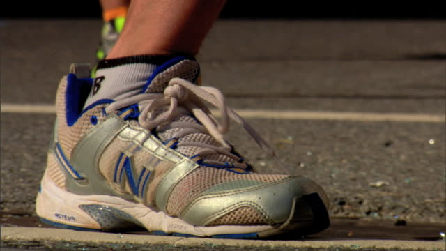 various unidentifiable people's feet in sneakers running jogging toward frame on concrete pavement street runners long distance foot race sports - race distance stock videos & royalty-free footage