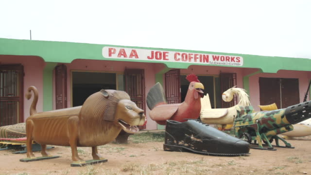 various unusually designed coffins stand outside a coffin makers workshop in accra. - 棺点の映像素材/bロール