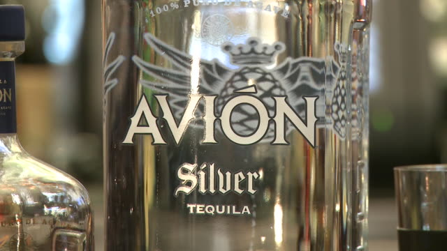 stockvideo's en b-roll-footage met various views and angles of avion tequila bottles on display at bar - avion