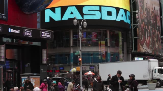 various views and exteriors of nasdaq entrance in times square / commuters and tourists walking past / various angles of signage / digital ads on... - ナスダック点の映像素材/bロール