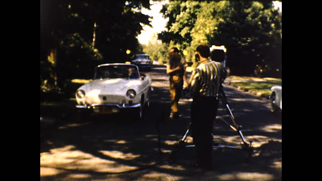 """various views of a red bus on the road in the shade """"tele-tape productions""""; various views of men operating a film camera on the road shooting a... - full suit stock videos & royalty-free footage"""