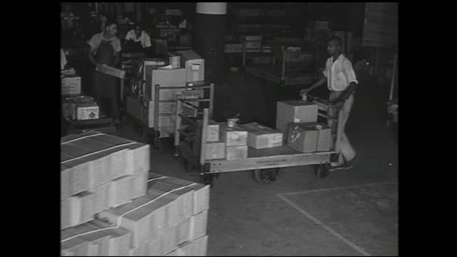 various views of boxes and cargo being loaded and transported by workers onto trucks; spools of cable being loaded - 1940 1949 stock videos & royalty-free footage
