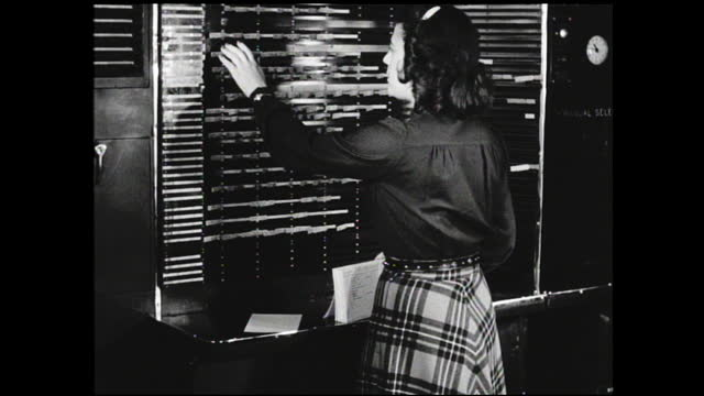 various views of woman organizing labels on the scheduling board; hand holding file card in front of camera - 1940 1949 video stock e b–roll
