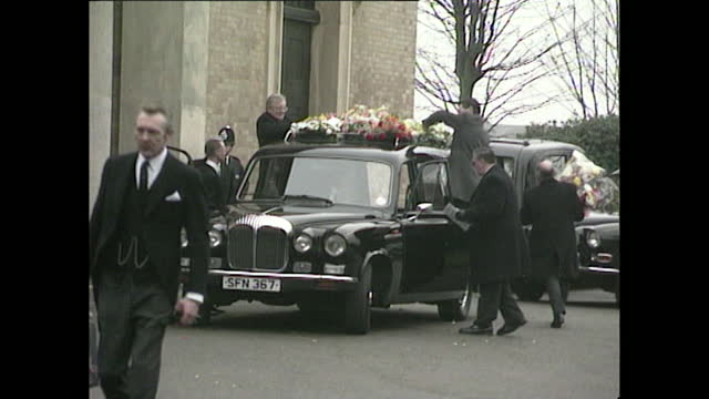 various views outside church holding freddie mercury's funeral service. shots include a hearse covered in wreaths, elton john dressed in black and... - elton john stock videos & royalty-free footage