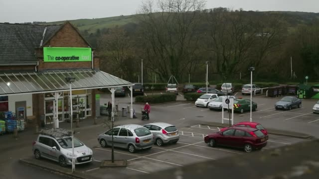various wide high angle views co operative food store, operated by the co operative group ltd, shoppers entering and exiting, cars driving through... - catena di negozi video stock e b–roll