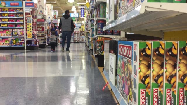 various wide, medium and close shots of toys r us, with families and their kids browsing through the toys and buying some. - toys r us stock videos & royalty-free footage