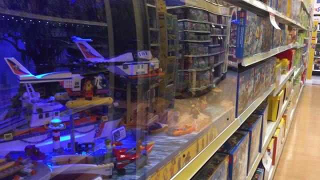 various wide medium and close shots of toys r us with families and their kids browsing through the toys and buying some - toys r us stock videos and b-roll footage