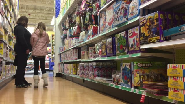stockvideo's en b-roll-footage met various wide medium and close shots of toys r us with families and their kids browsing through the toys and buying some - speelgoed