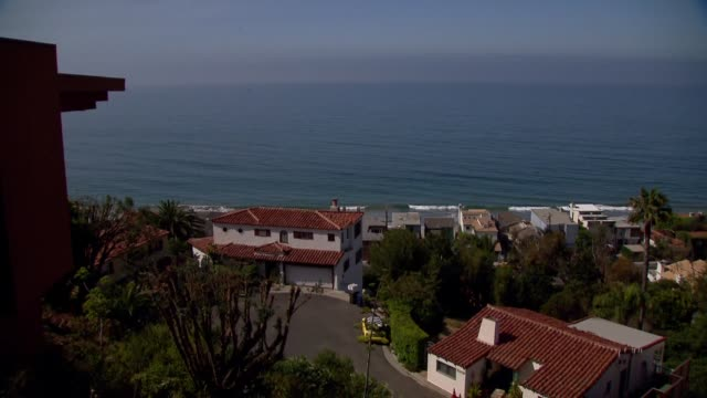 various wide scenic shots of the pacific coast in malibu california on july 18 a wide shot of homes along the pacific coast with a hill behind them... - pazifikküste stock-videos und b-roll-filmmaterial