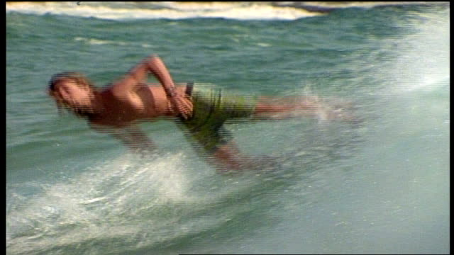 various wide shot of men riding skimboards in california - skimboard stock videos and b-roll footage