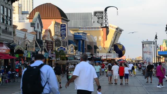 Various wide shots of a crowded Atlantic City boardwalk on a sunny evening in Atlantic City New Jersey
