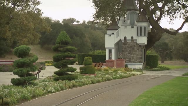 various wide shots of the train tracks running through a garden with picnic tables and a castle in the background at the neverland ranch property in... - ネバーランドバレーランチ点の映像素材/bロール