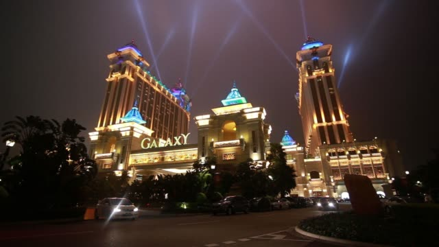 Various wide views of the illuminated building exterior and signage of the Galaxy Macau casino resort operated by Galaxy Entertainment Group Ltd at...